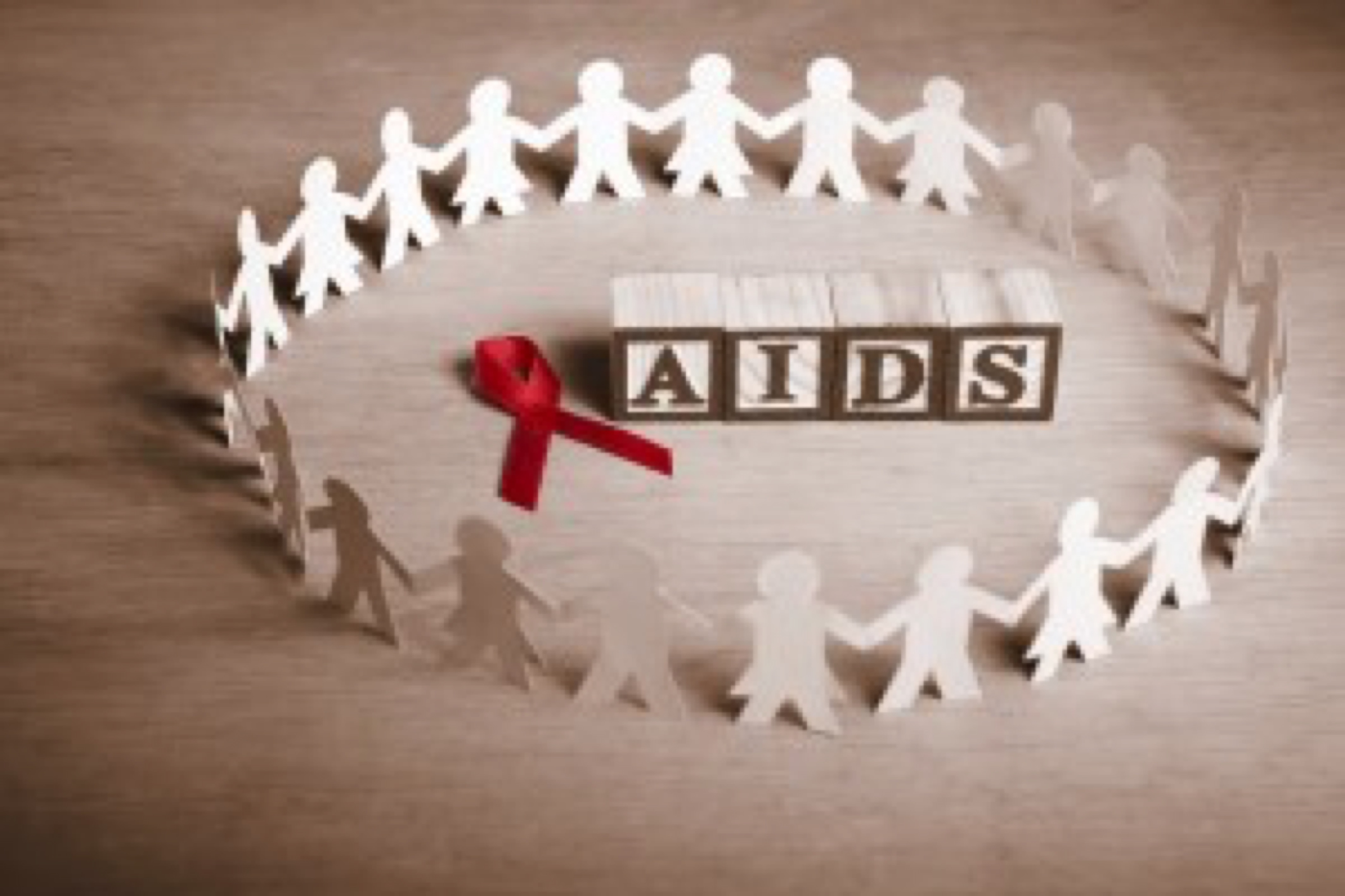Red ribbon with word 'AIDS' surrounded by couple paperdolls