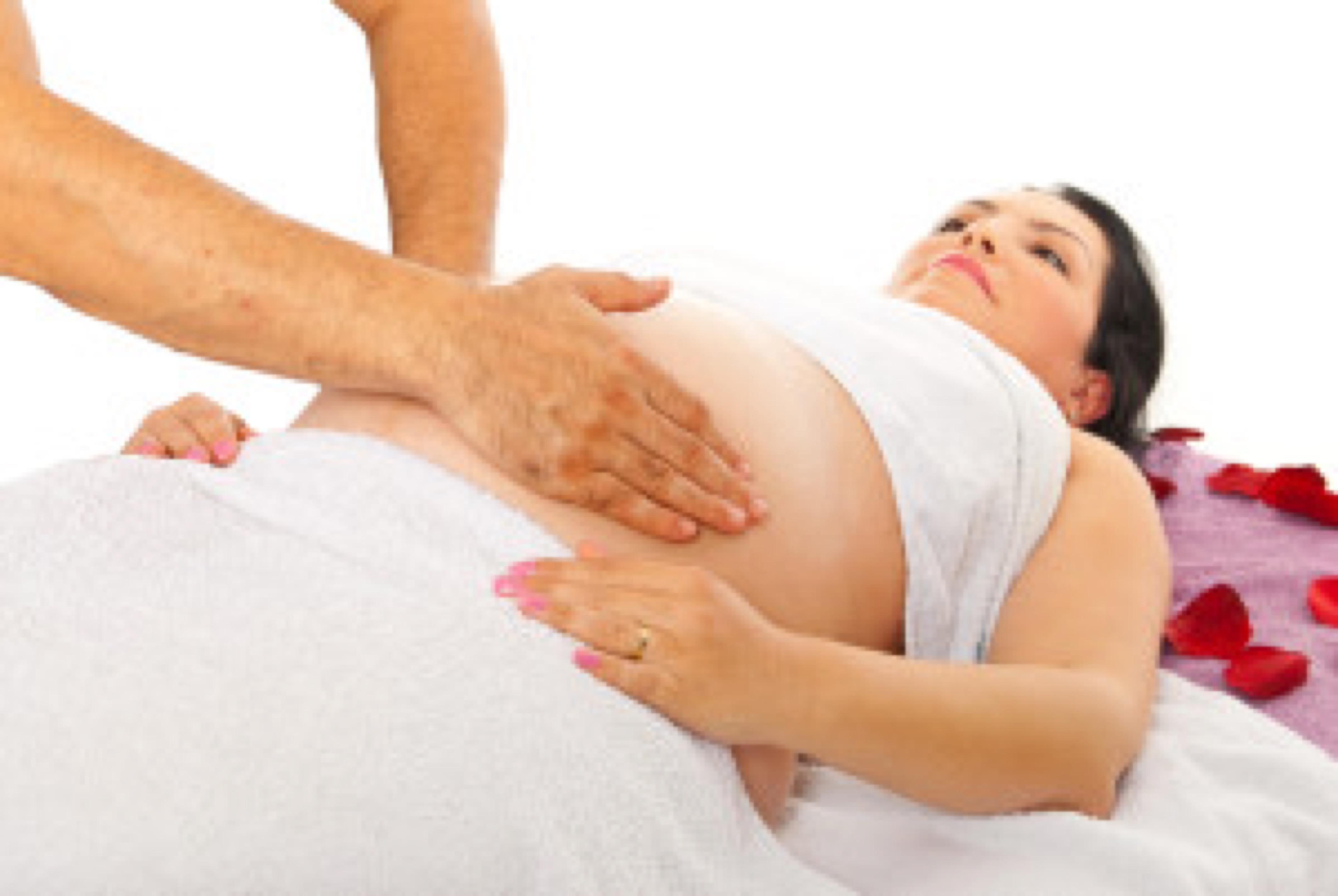 Therapist doing massage to pregnant woman tummy against white background