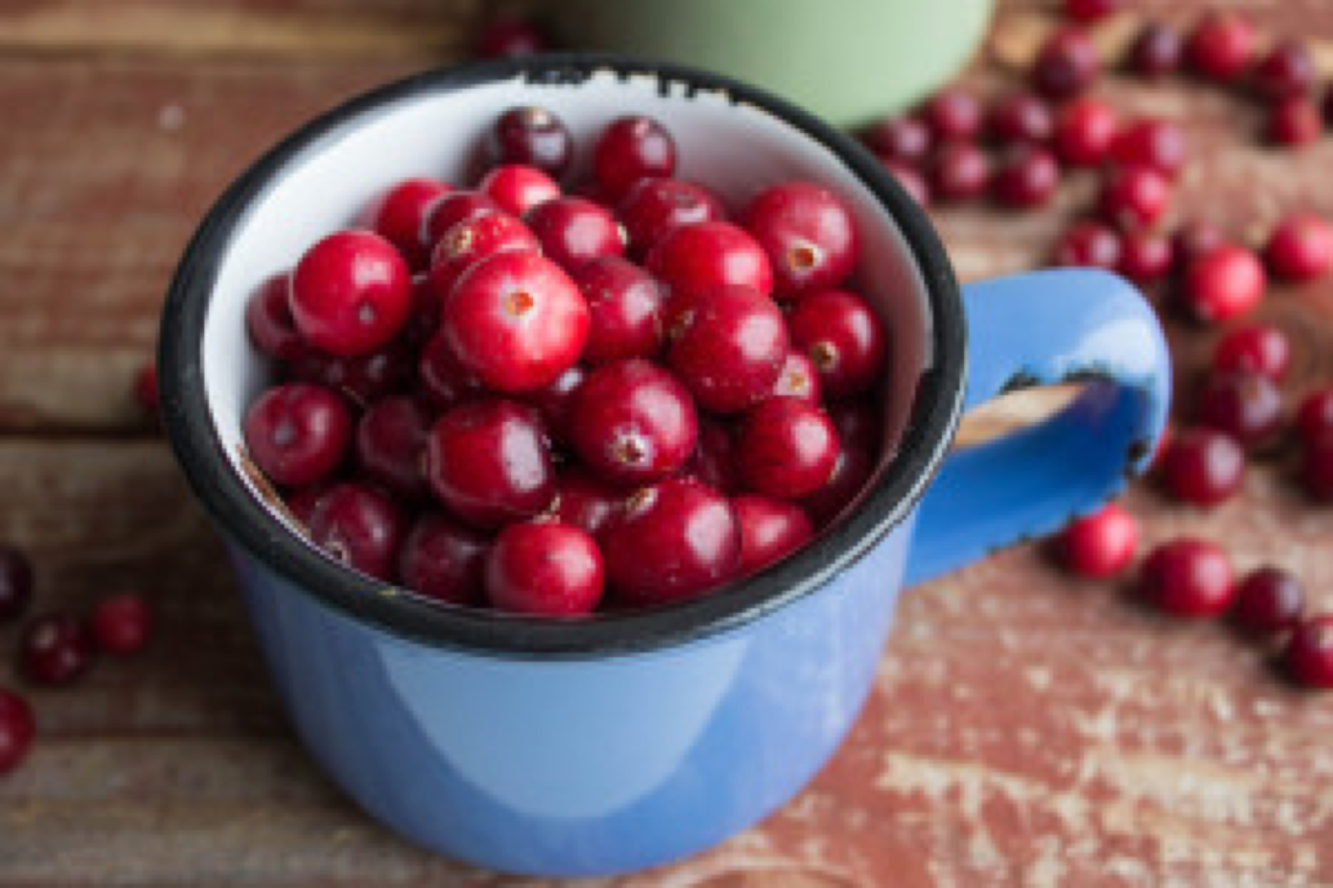 ripe cranberries in cups on a wooden surface