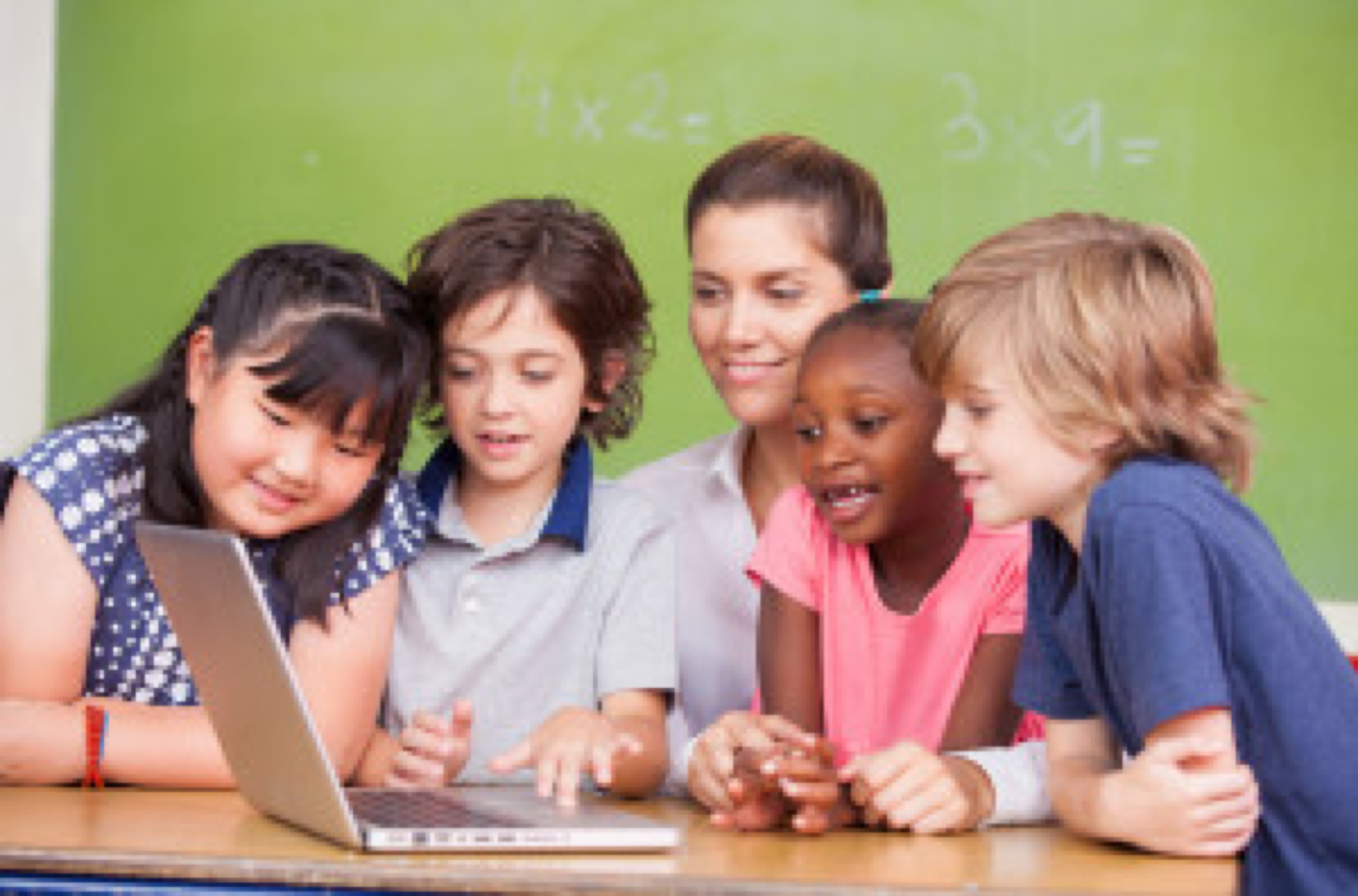 Interracial primary classroom learning to use laptop with their teacher.