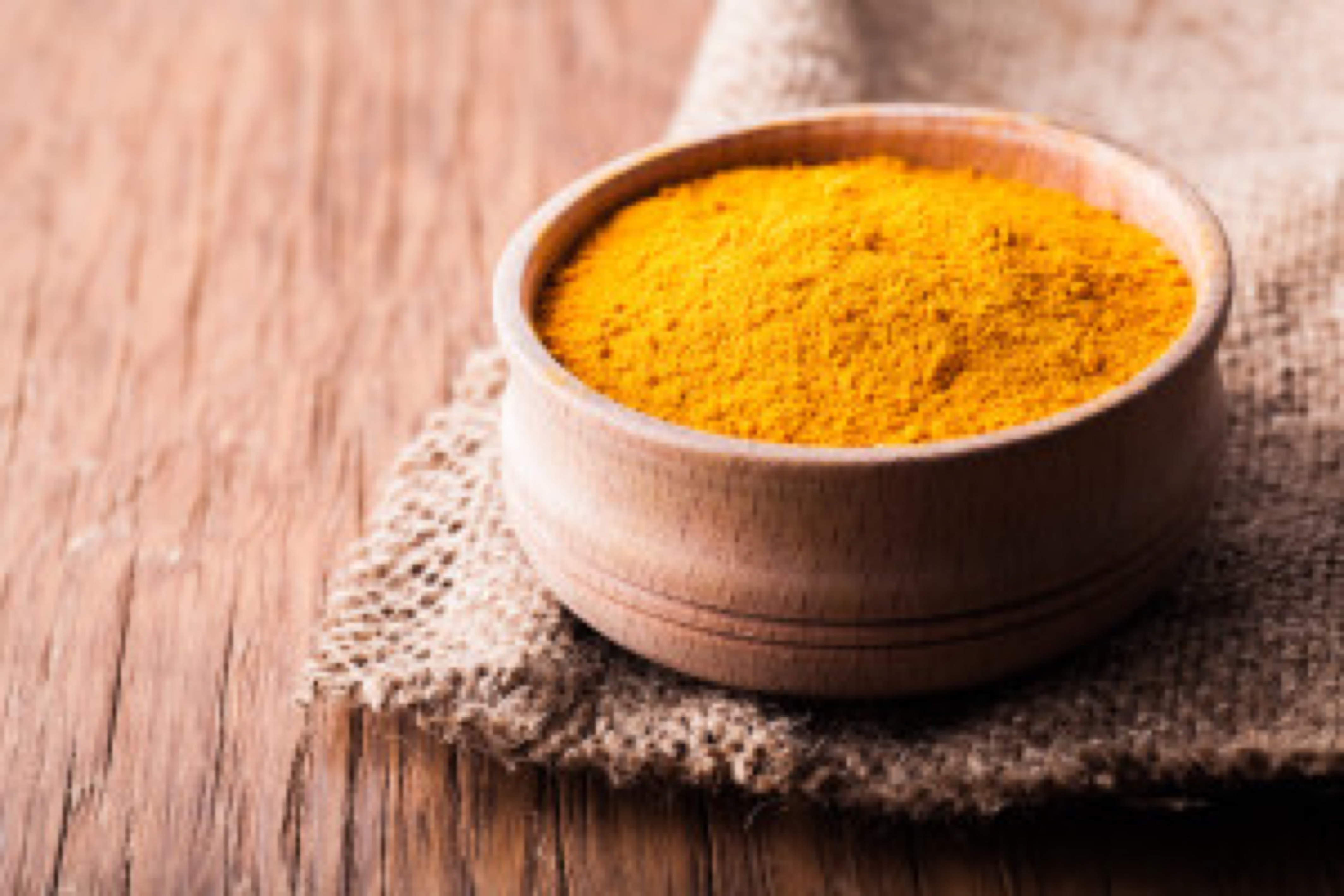dry spice turmeric in a wooden bowl close-up on a vintage background