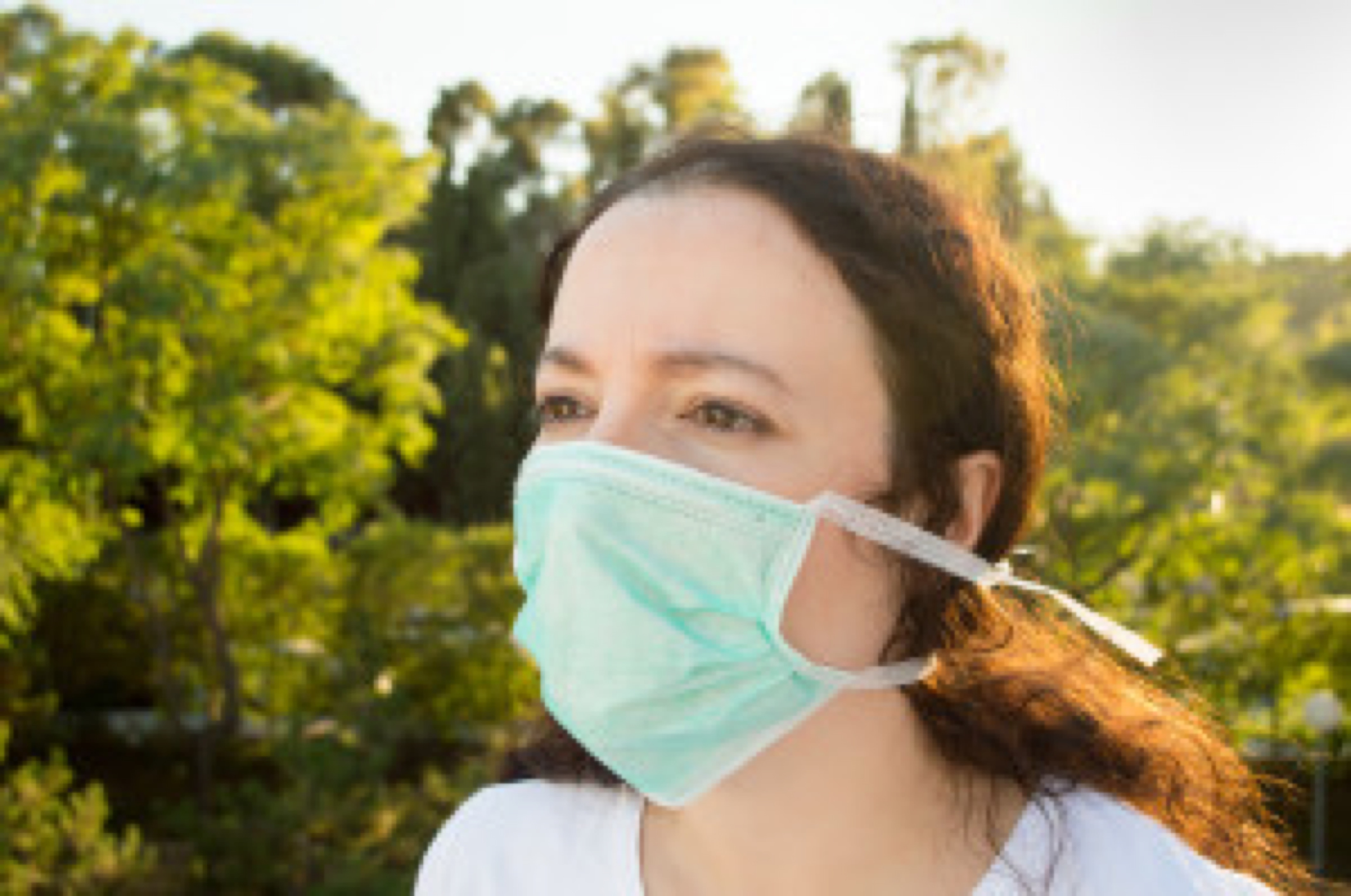 close up of an unhappy woman wearing a face mask to deal with virus or pollution
