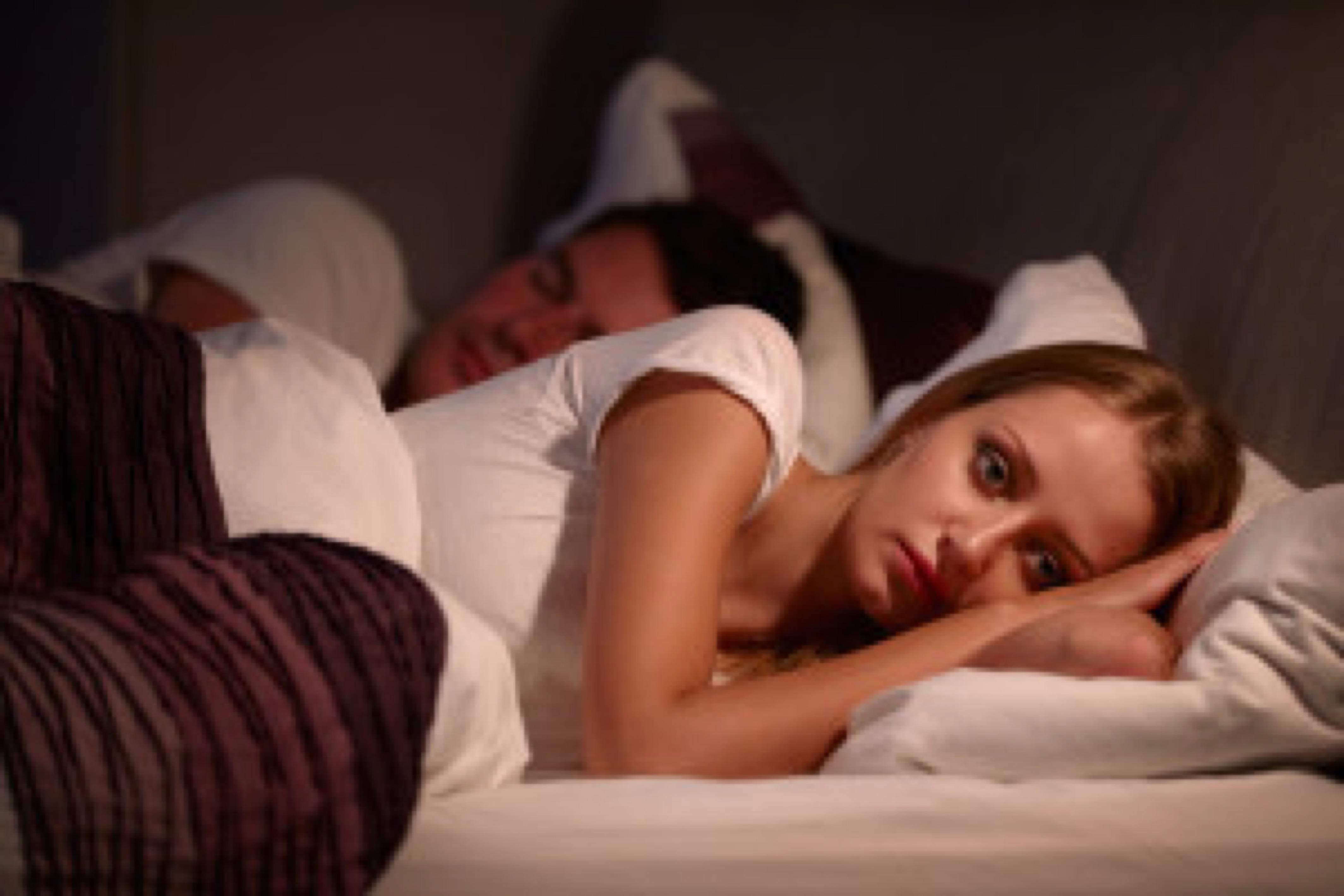 Woman Lying Awake In Bed Suffering With Insomnia