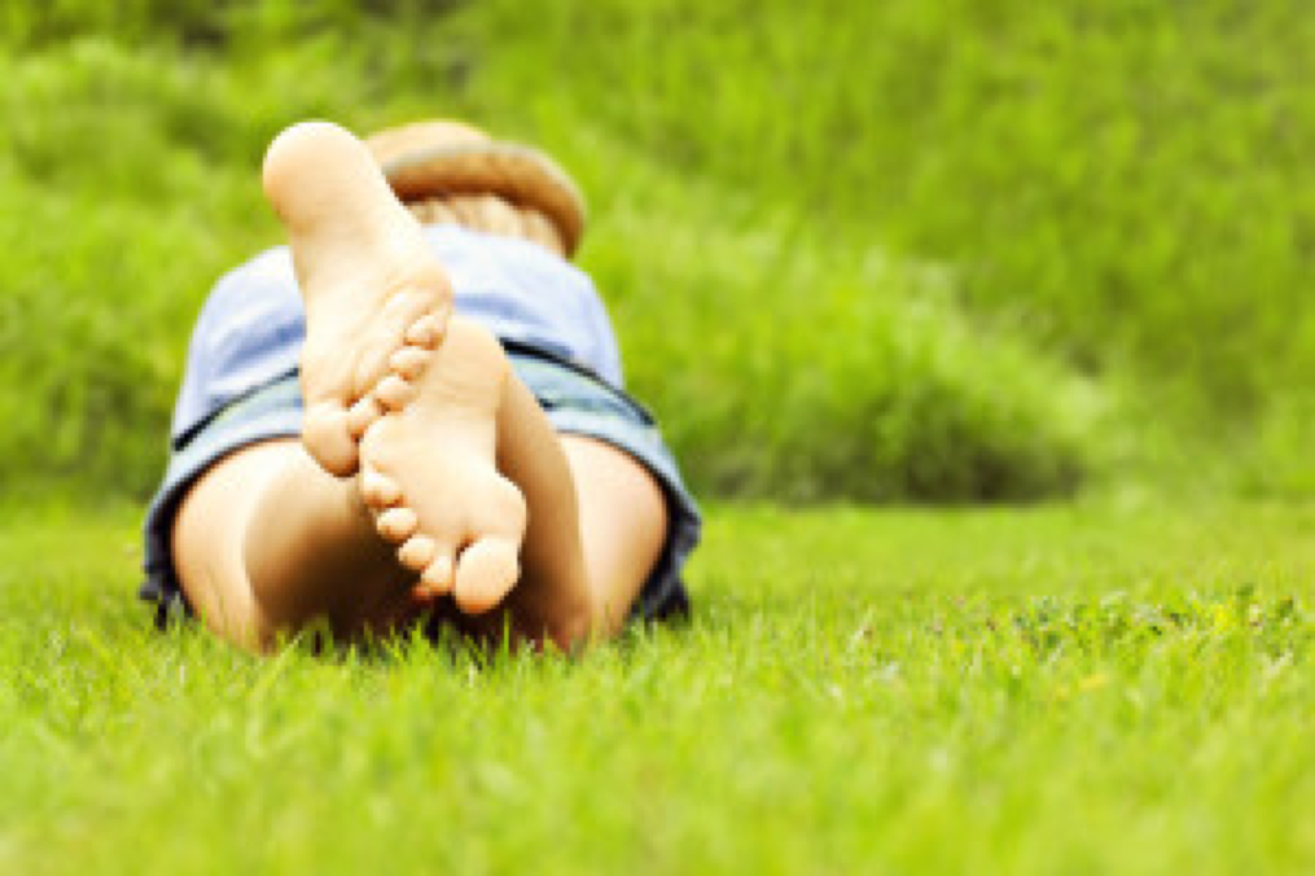 A back picture of a woman lying on green grass with copy space on the right