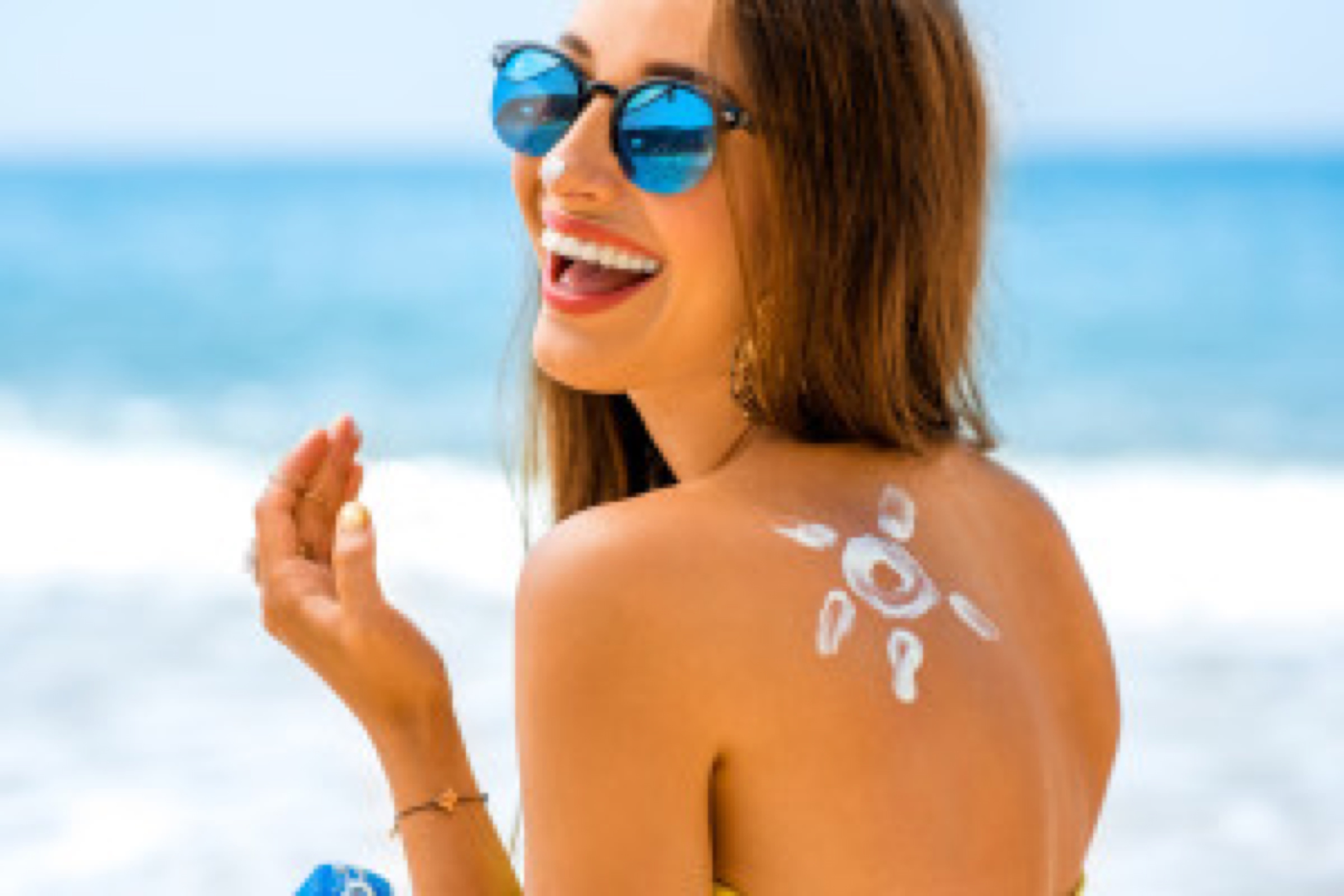 Young woman with sun shape on the shoulder holding sun cream bottle on the beach