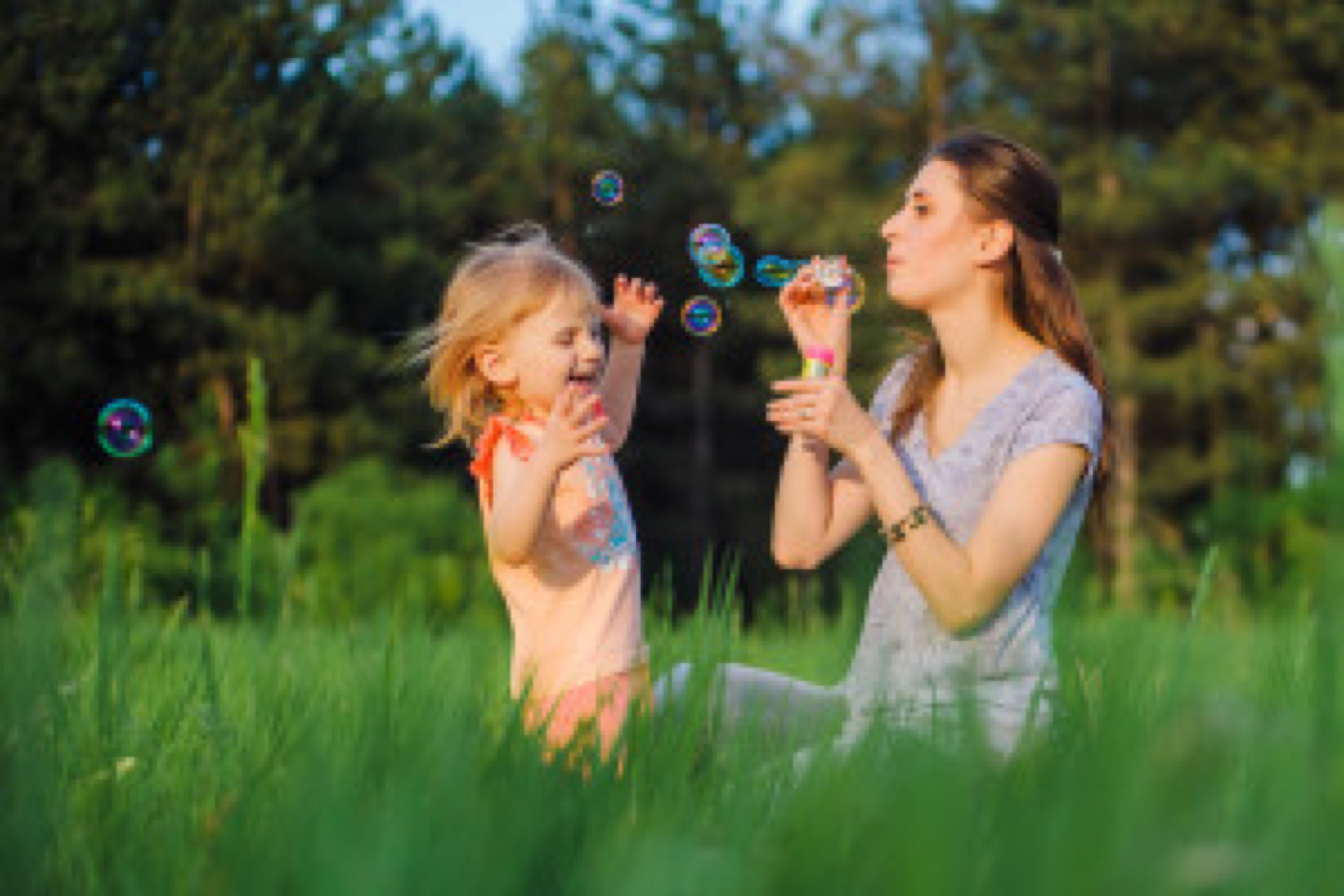 Mom and daughter blow bubbles