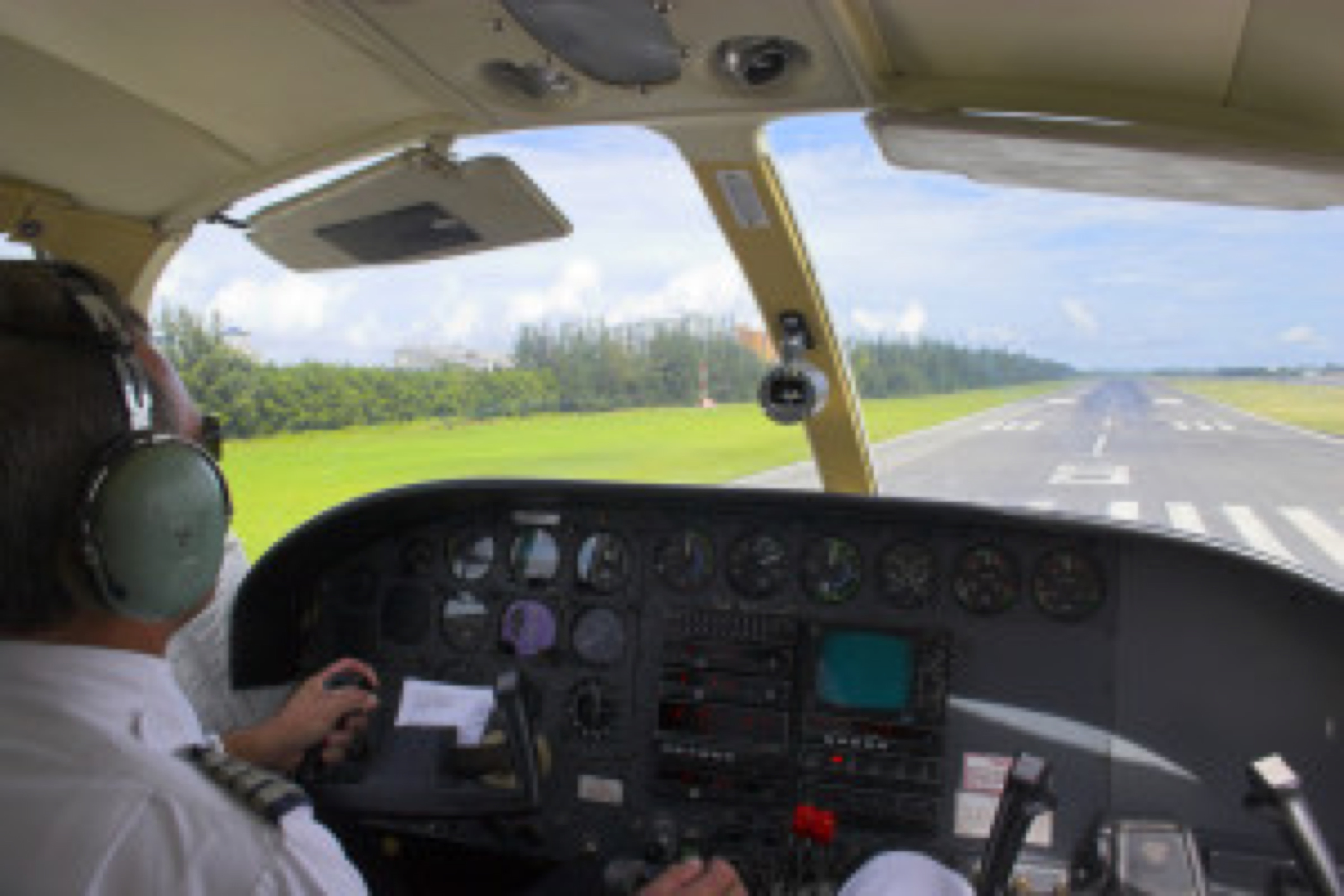 Small plane pilot flying and landing over tropical island in Caribbean