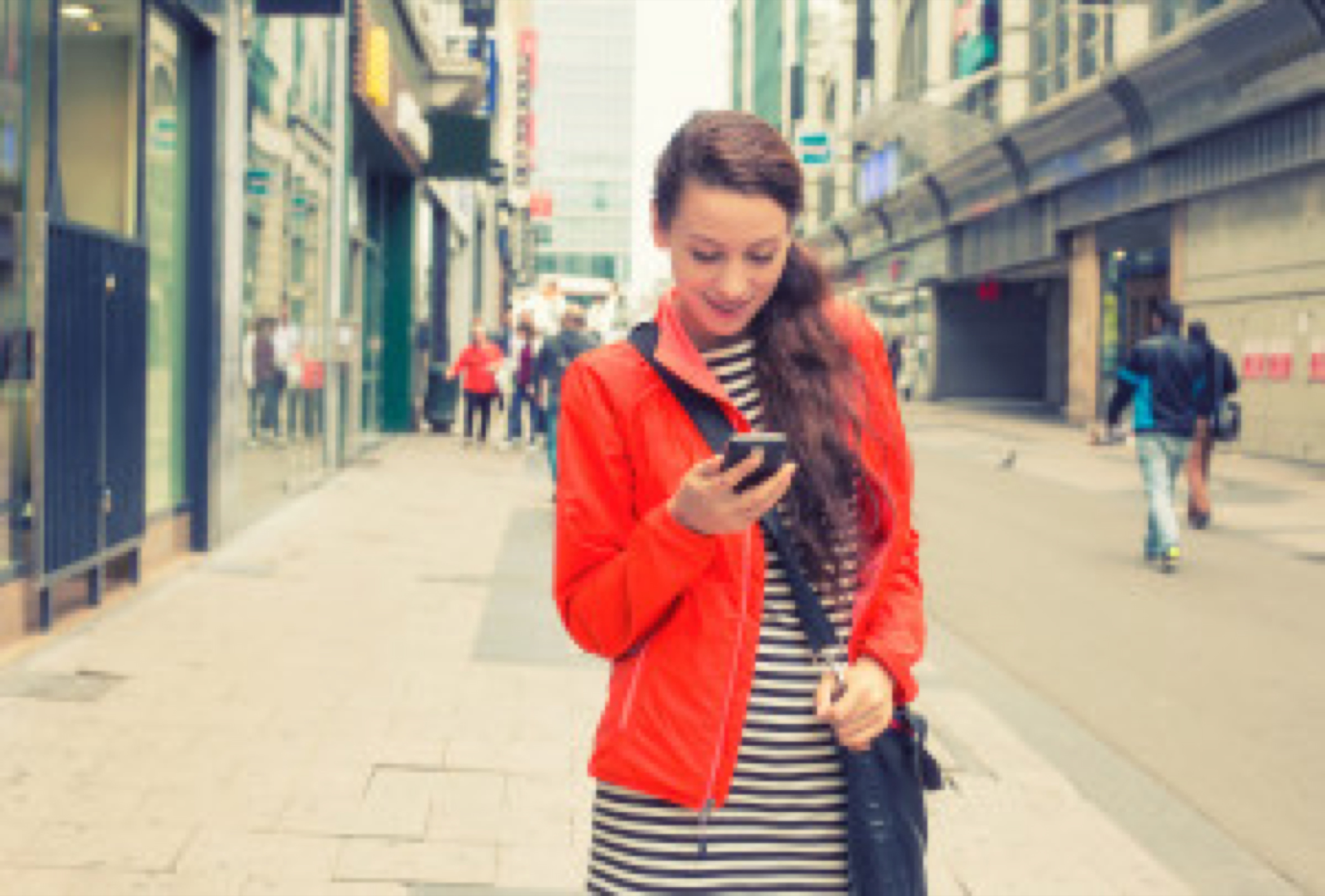 Happy girl texting on the smart phone walking down the street wearing a red jacket in autumn