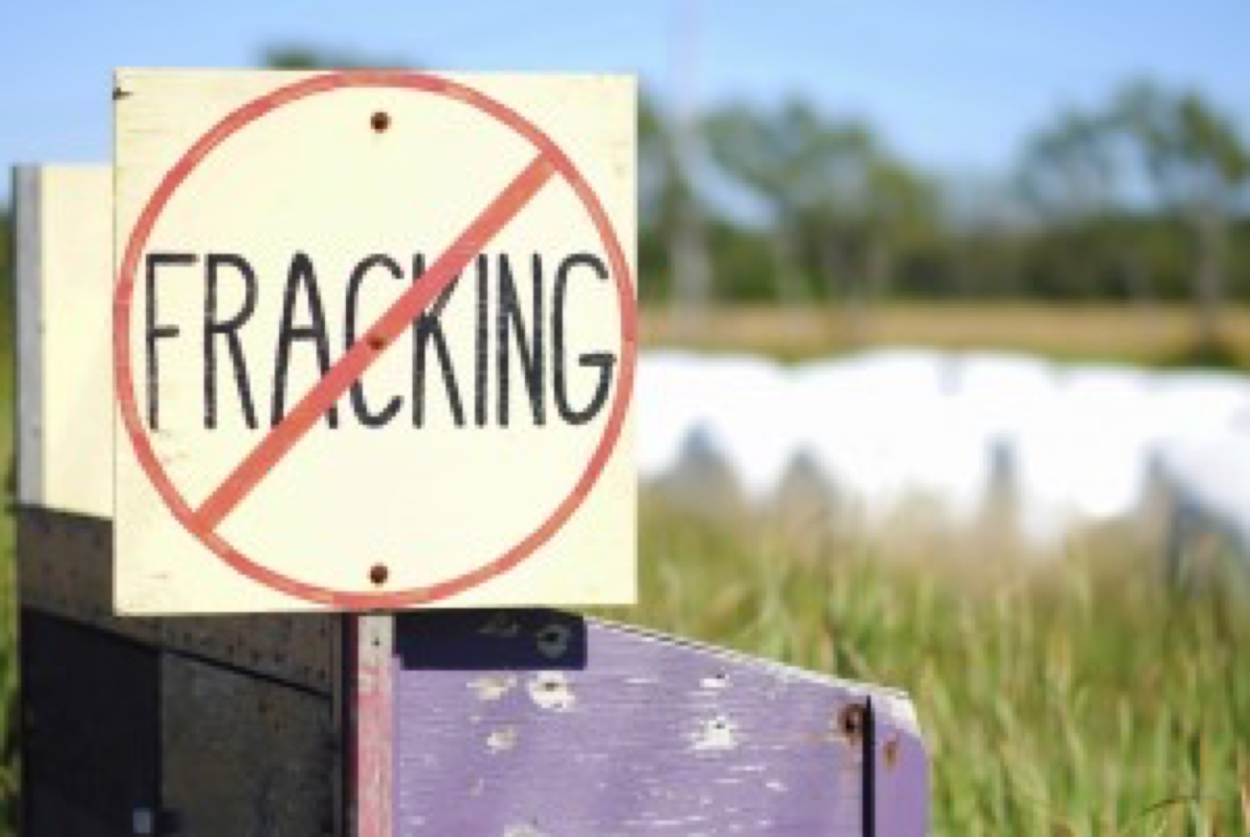 Hand-painted No Fracking Sign in Rural Setting, farmland and hay bales in background