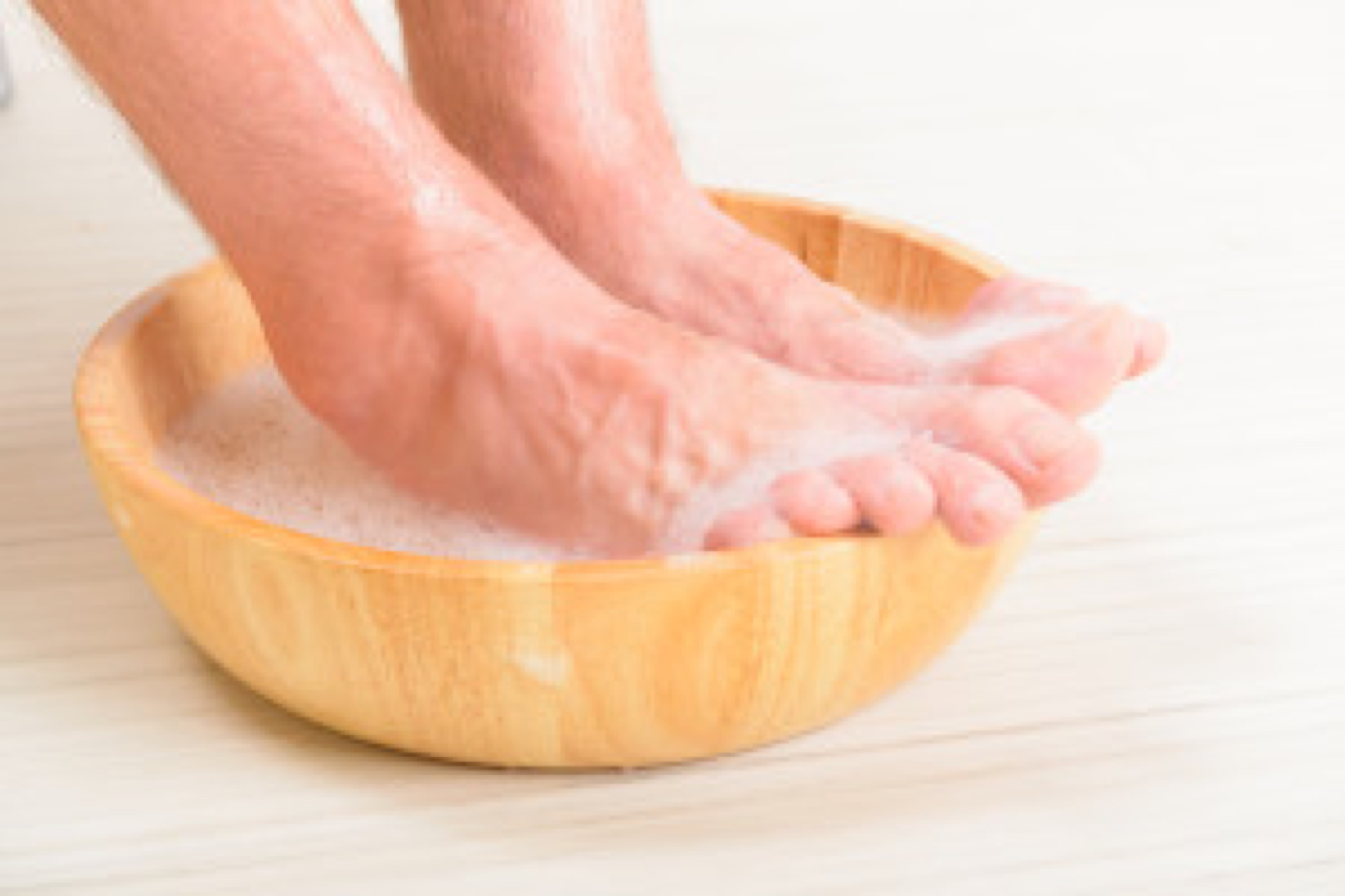 Male feet in a bowl with water and soap, hygiene and spa concept