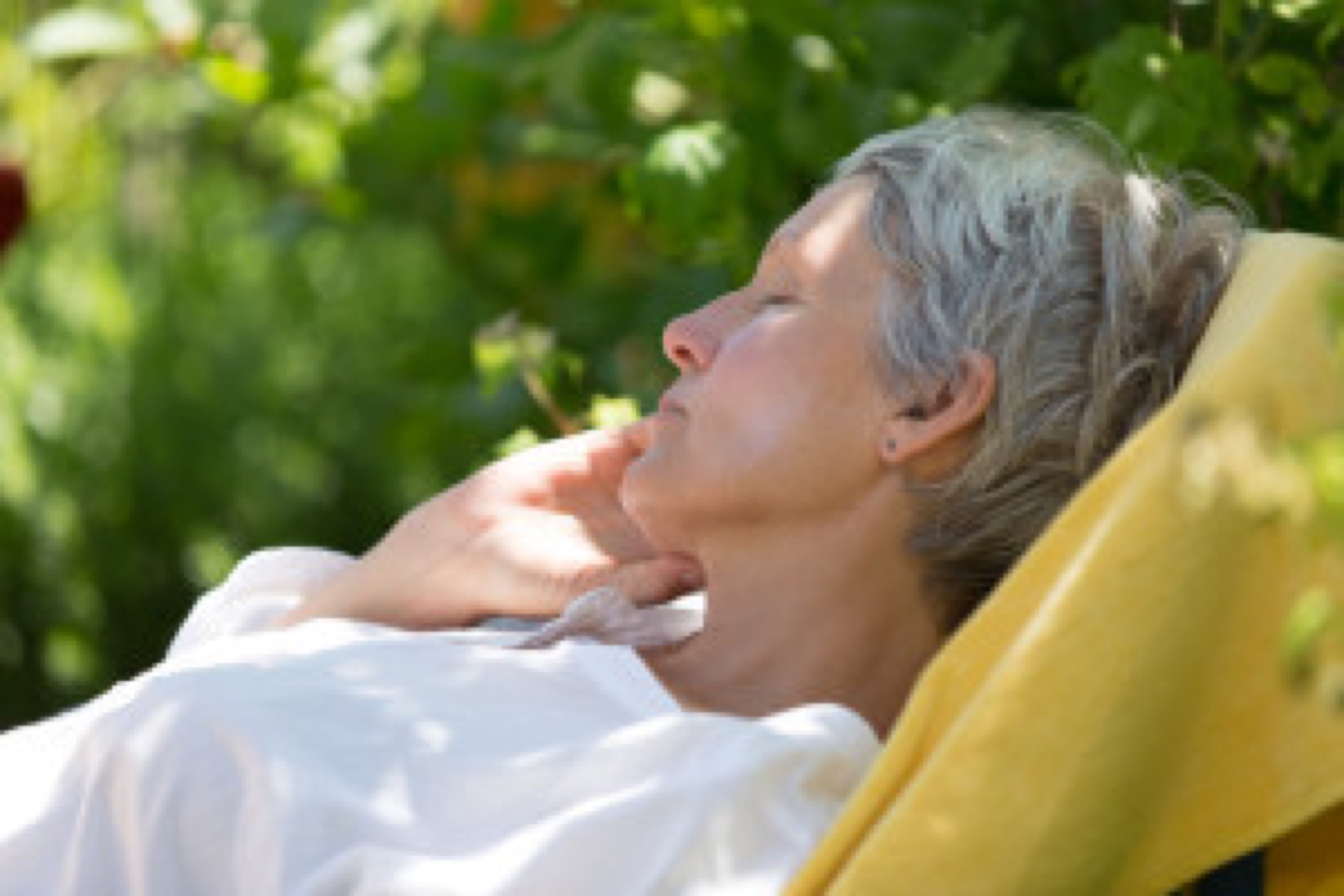 Aged woman with white hairs sleeping on lounger in her garden.