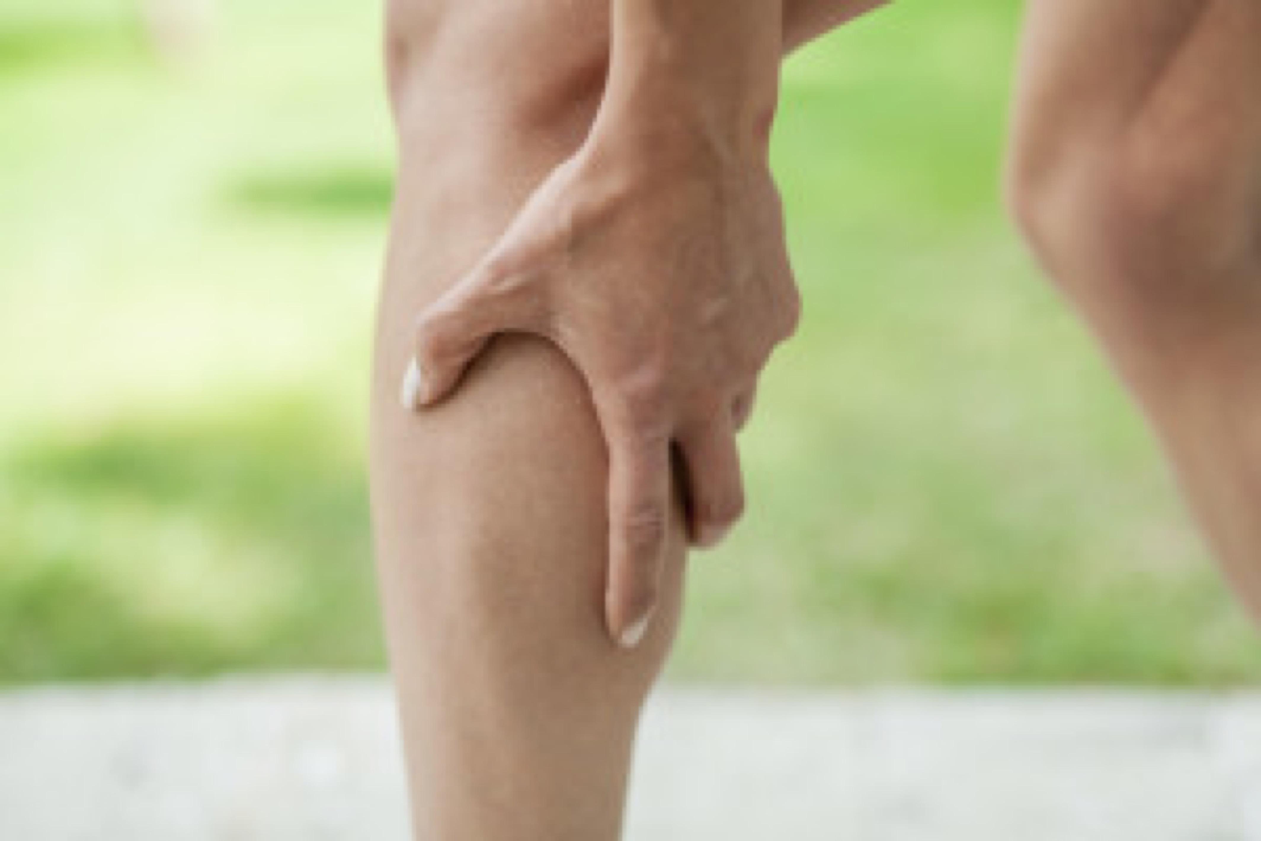 Woman holding sore leg muscle