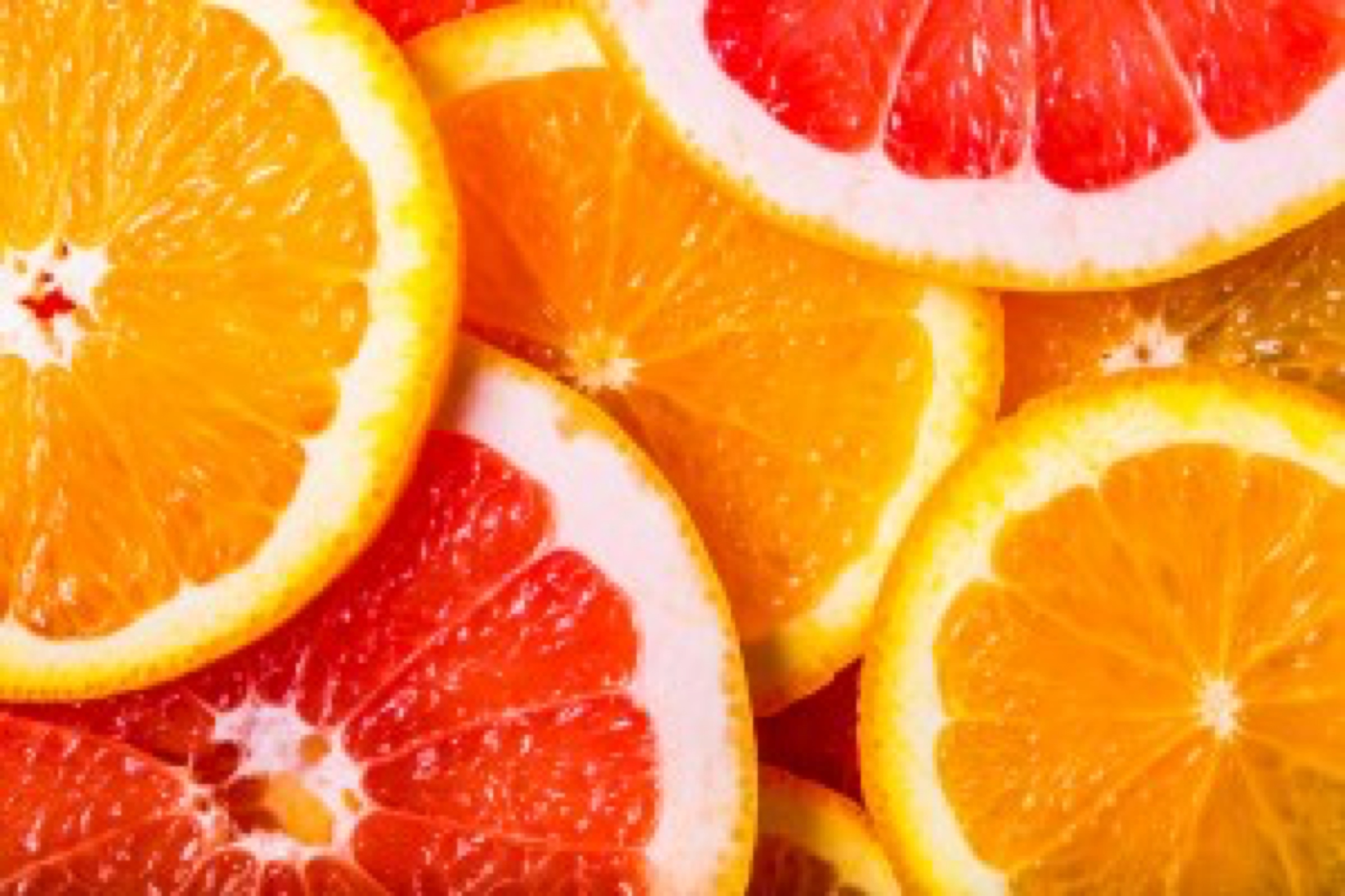 background made with a heap of sliced oranges and grapefruits