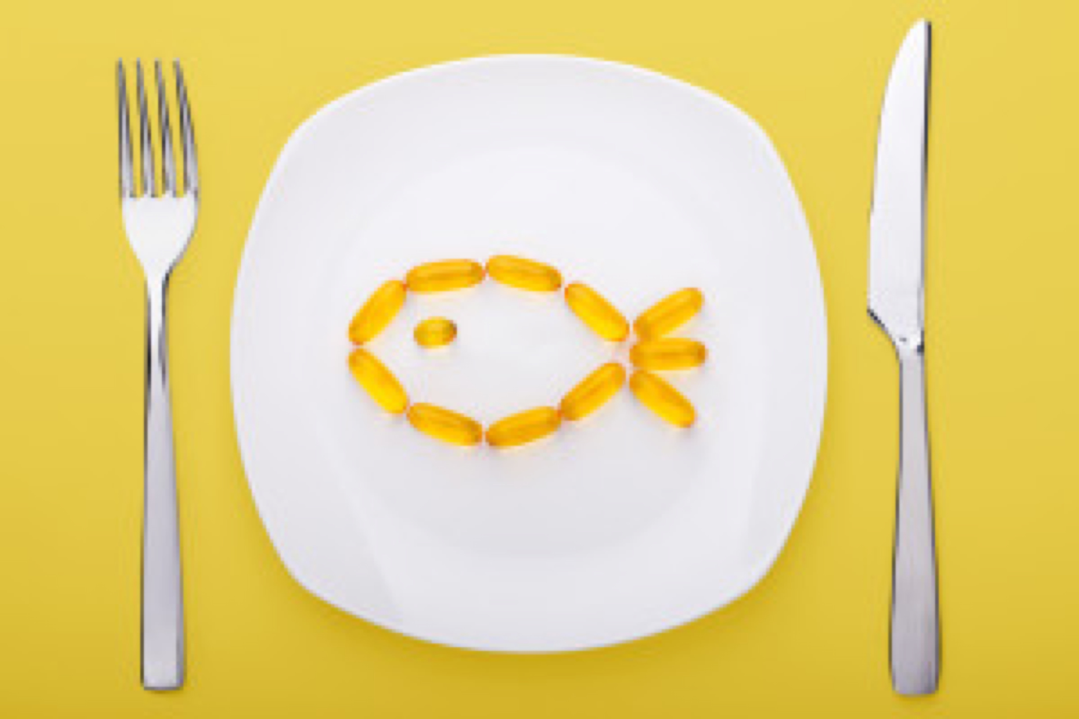 fish oil soft gels lying on white porcelain plate in the form of fish (yellow background)