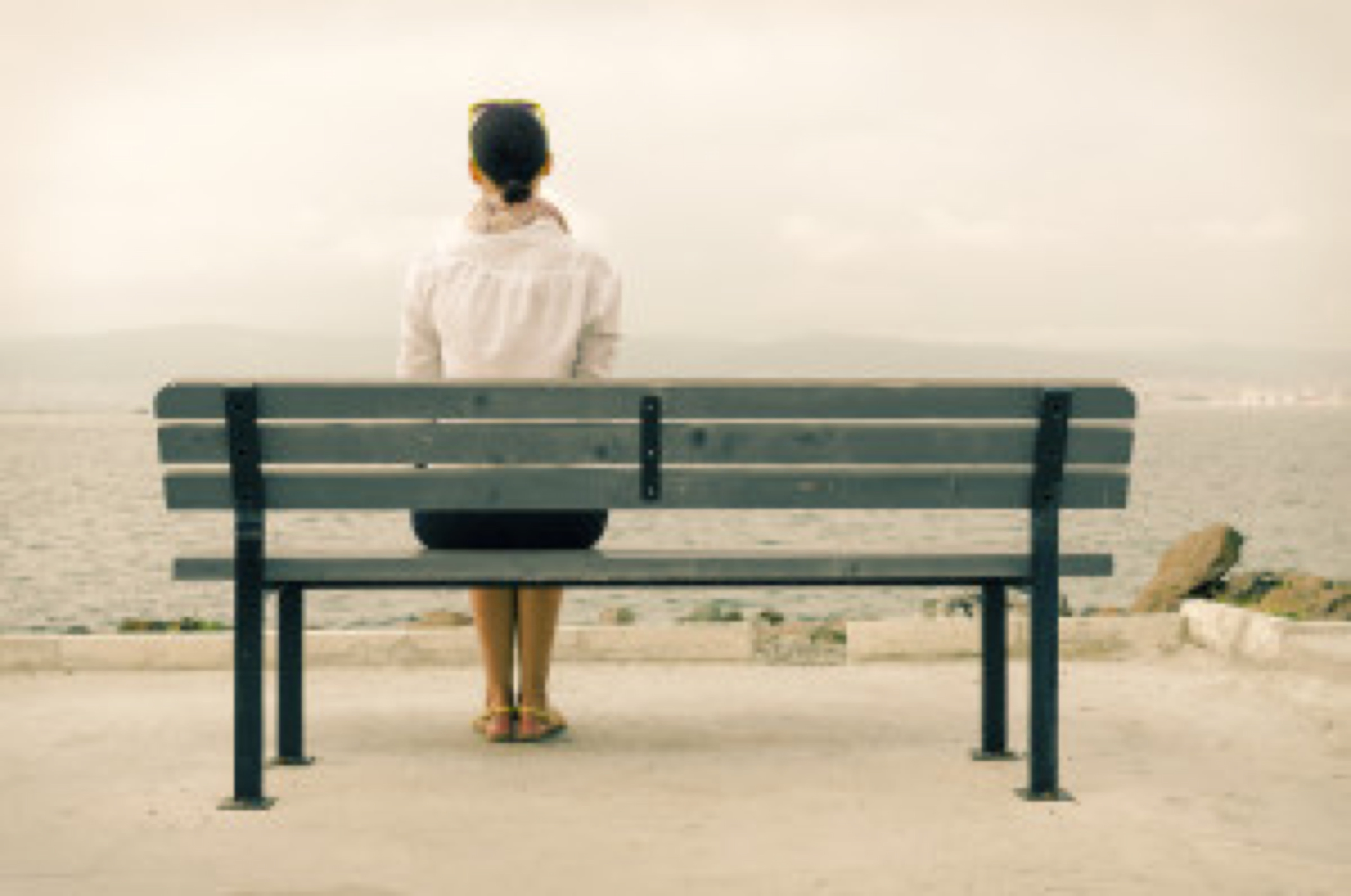 Lonely woman sitting on a bench by the sea