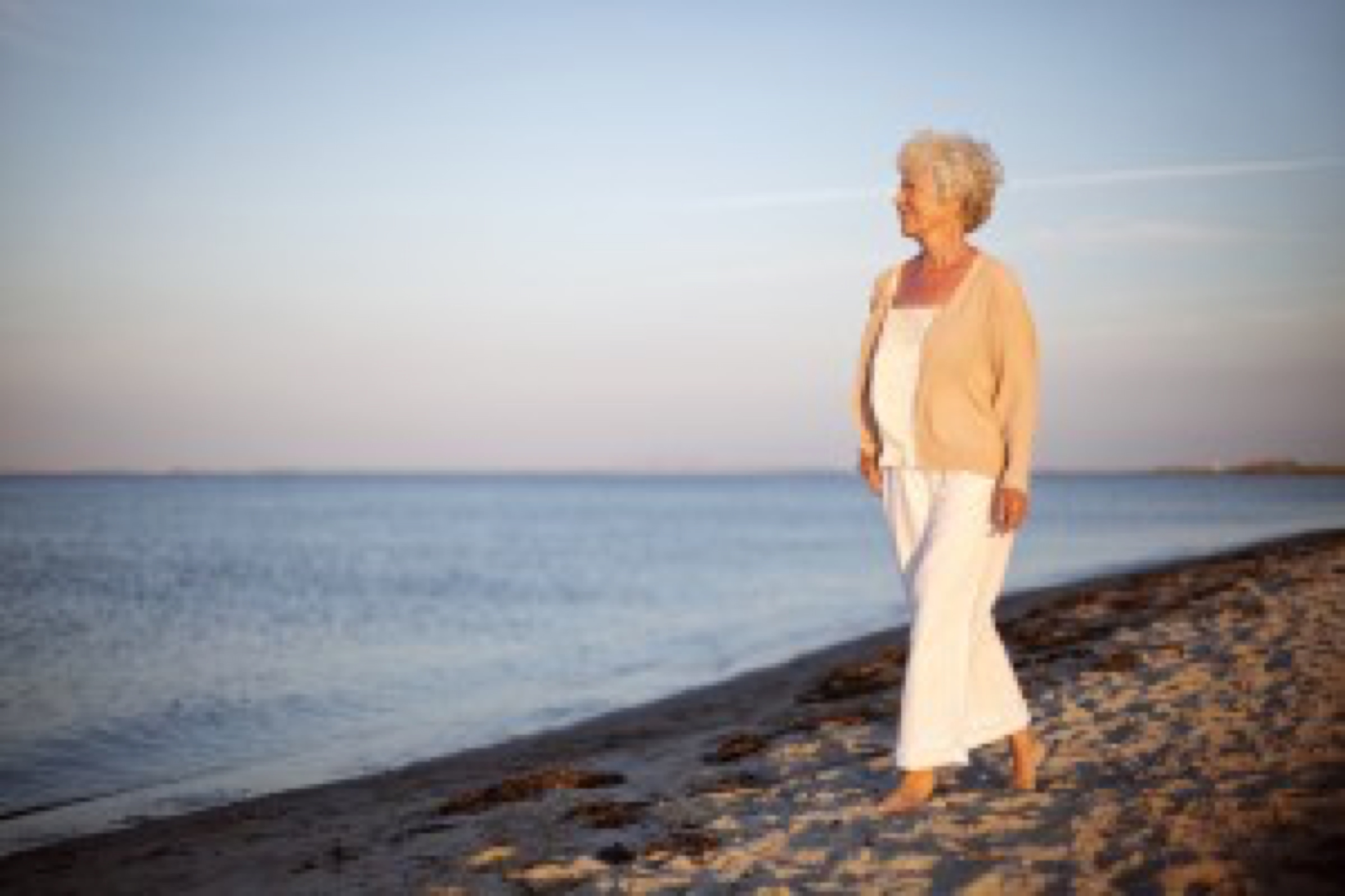 Portrait of a mature woman walking on the beach looking at the sea. Relaxed old lady strolling on the beach with lots of copyspace.
