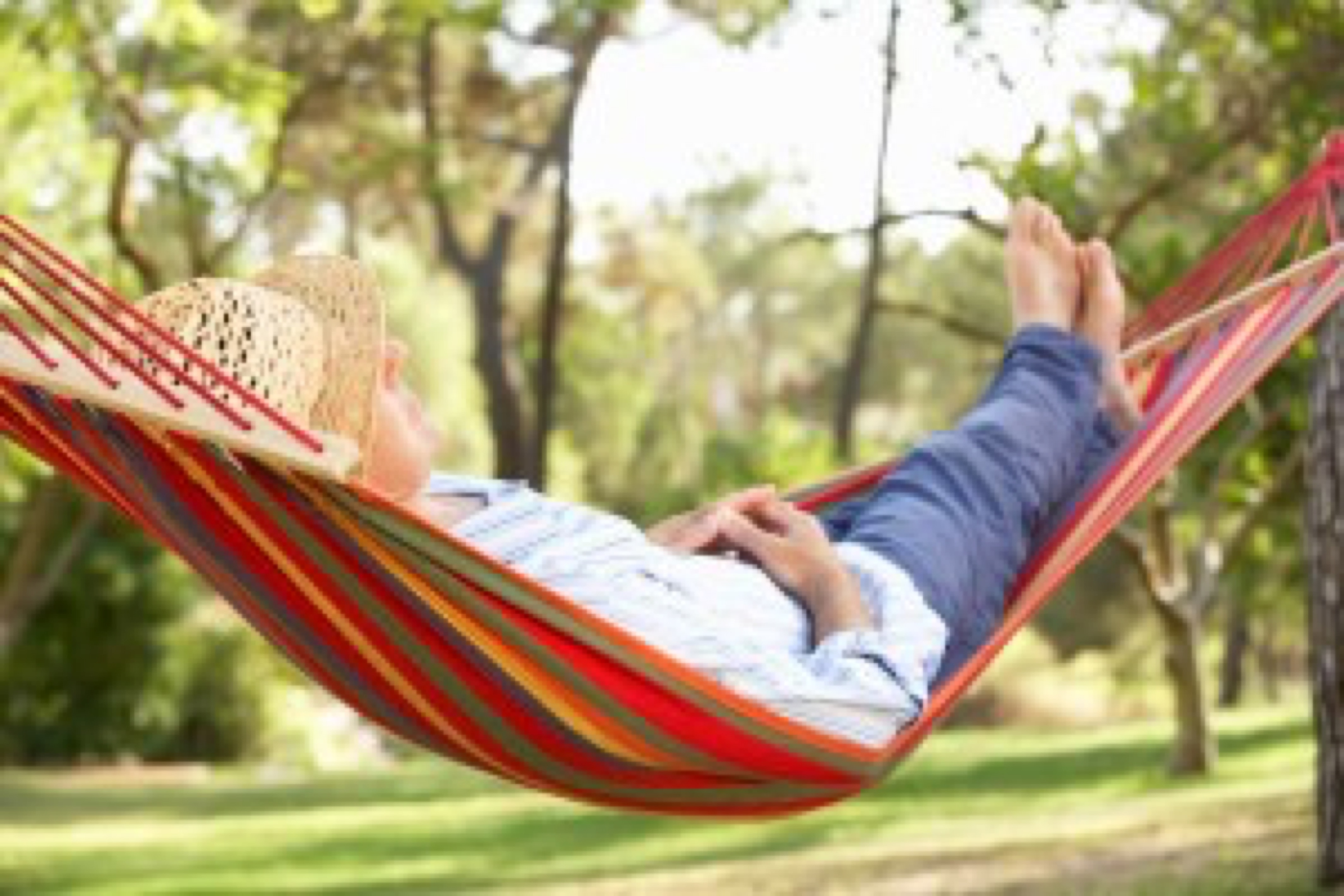 Senior Man Relaxing In Hammock Alseep In Sunshine