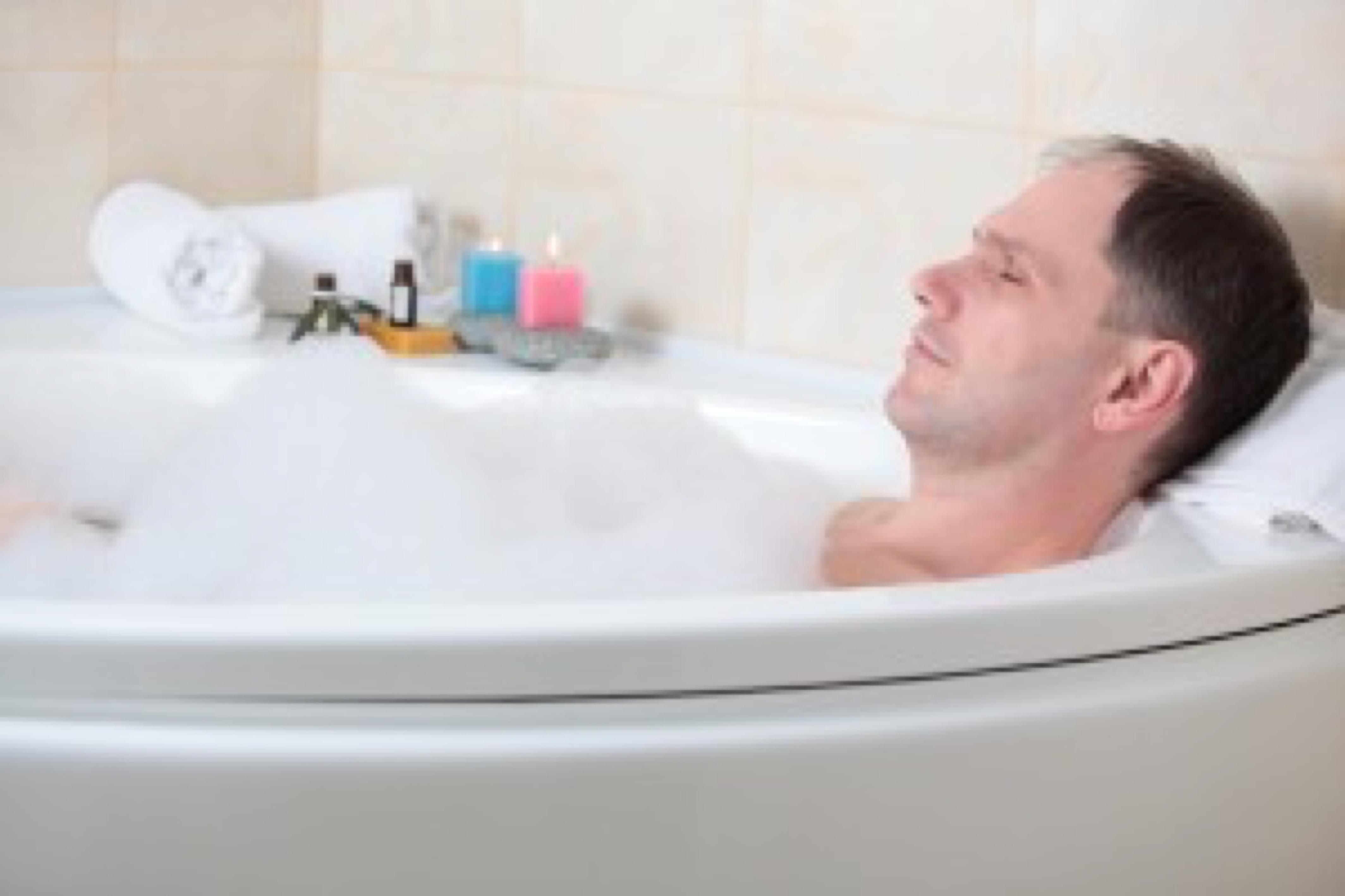 Adult man having a bath with essential oil