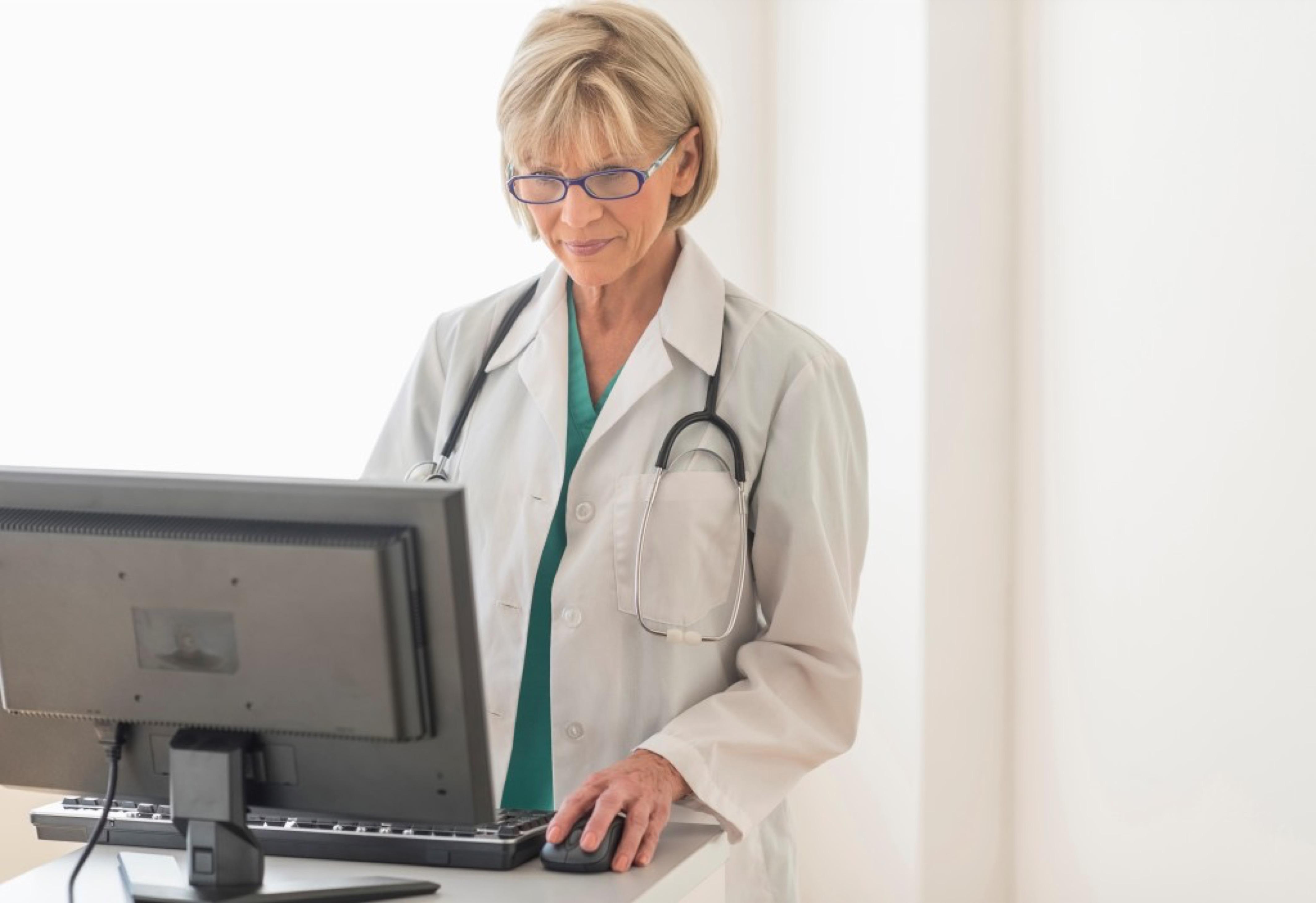Mature female doctor using desktop PC at desk in hospital