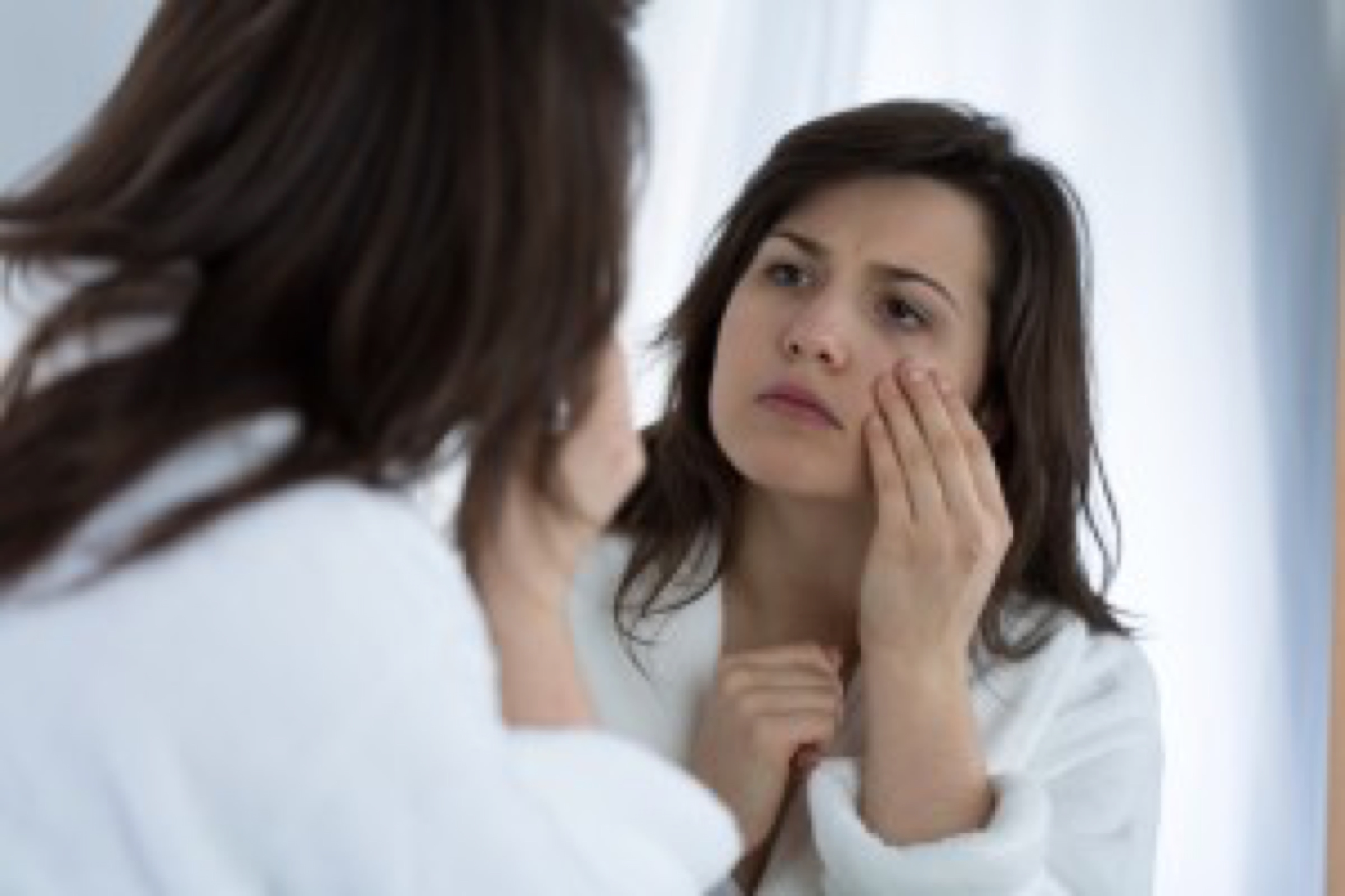 Young sad woman looking in the mirror at her wrinkles